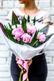 Frau mit Blumenstrauß von rosa Pfingstrosen im Kraftpapier Stockfotos