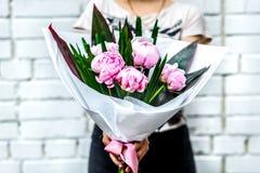 Frau mit Blumenstrauß von rosa Pfingstrosen im Kraftpapier Stockbild