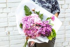 Frau mit Blumenstrauß von rosa Pfingstrosen im Kraftpapier Stockfoto