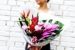 Frau mit Blumenstrauß von rosa Pfingstrosen im Kraftpapier Lizenzfreie Stockfotografie