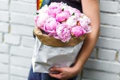 Frau mit Blumenstrauß von rosa Pfingstrosen im Kraftpapier Stockbilder