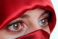 Frau mit braunen Augen und rotem Schleier Stockfotografie
