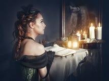 Frau mit Buch im Retro- Kleid und im Geist im Spiegel Stockbilder