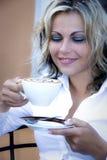 Frau mit Cappuccinokaffee lizenzfreie stockbilder