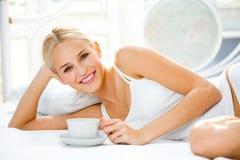 Frau mit Cup auf Bett Stockfotos