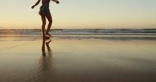 Frau mit dem Arme ausgestreckten Gehen auf Strand stock footage