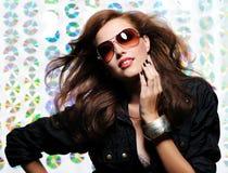 Frau mit dem Auflockern der Haare und der Art und Weisesonnenbrillen Lizenzfreies Stockbild