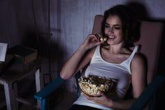 Frau mit dem aufpassenden Film und Lachen des Popcorns Stockfotografie
