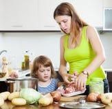 Frau mit dem Baby, das mit Fleisch kocht Stockbild