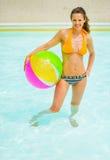 Frau mit dem Ball, der im Swimmingpool steht Lizenzfreies Stockfoto