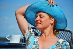 Frau mit dem blauen Hut, der Kaffee auf dem Strand trinkt Lizenzfreies Stockfoto
