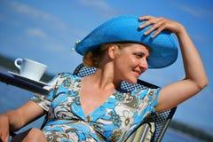 Frau mit dem blauen Hut, der Kaffee auf dem Strand trinkt Lizenzfreie Stockfotos