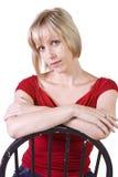 Frau mit dem blonden Haar, das auf Stuhl sitzt Lizenzfreie Stockbilder