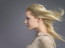 Frau mit dem blonden Haar, das im Wind durchbrennt Stockfoto
