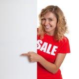 Frau mit dem blonden Haar in einem Verkauf shirtbehind ein Schild Stockfotografie
