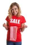 Frau mit dem blonden Haar in einem Verkaufhemd, das eine Einkaufstasche hält Stockbilder