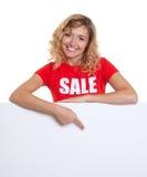 Frau mit dem blonden Haar in einem Verkaufshemd zeigend auf ein Schild Stockfotografie