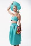 Frau mit dem blonden Haar im russischen nationalen Hut, der matrioshka Puppe hält Lizenzfreies Stockbild