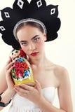 Frau mit dem blonden Haar im russischen nationalen Hut, der matrioshka Puppe hält Stockbilder