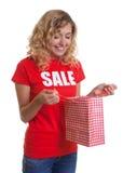 Frau mit dem blonden Haar und Einkaufstasche in einem Verkaufhemd Lizenzfreies Stockfoto