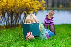 Frau mit dem Buch, das auf dem Gras liegt Lizenzfreies Stockfoto