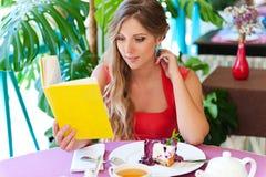 Frau mit dem Buch, das im Kaffee sitzt Stockbilder