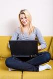 Frau mit dem Computer, der auf Couch sitzt Stockfoto