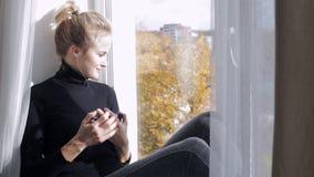Frau mit dem eBook, das auf dem Fensterbrett sitzt stock video footage