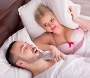 Frau mit dem Ehemann, der im Schlaf schnarcht Stockbilder