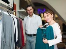 Frau mit dem Ehemann, der Kleidung wählt Stockbild