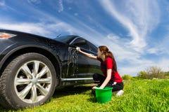 Frau mit dem Eimer, der schwarzes Auto auf dem Gebiet wäscht Lizenzfreie Stockfotografie