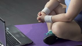 Frau mit dem Extragewicht, das auf Boden vor Laptop, on-line-Training sitzt stock footage