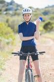 Frau mit dem Fahrrad, das Abfüller hält Stockfotografie