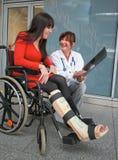 Frau mit dem Fahrwerkbein im Pflaster, in einem Arzt und im Stuhl Stockfotos
