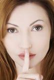 Frau mit dem Finger auf ihren Lippen. Stockfotografie