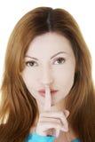 Frau mit dem Finger auf ihren Lippen. Stockfotos