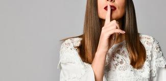 Frau mit dem Finger auf Lippen stockfotografie