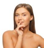 Frau mit dem Finger auf Lippen Stockbild