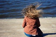 Frau mit dem Fliegen des blonden gelockten Haares auf Seehintergrund Stockbild