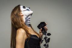 Frau mit dem furchtsamen Halloween-Skelettmake-up, das schwarze rosafarbene Blume über grauem Hintergrund hält stockfotos