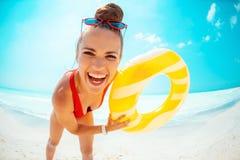 Frau mit dem gelben aufblasbaren Rettungsring, der Spaßzeit auf Strand hat lizenzfreie stockfotos