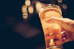 Frau mit dem gelben Nagel poliert, Glas kaltes Bier mit schönem bokeh halten lizenzfreie stockfotografie