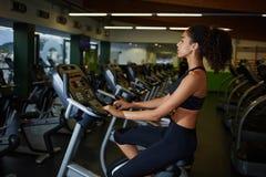 Frau mit dem gelockten Afrohaar, das auf Herz Simulatormaschine an der Turnhalle spinnt Stockfoto