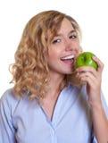 Frau mit dem gelockten blonden Haar einen grünen Apfel essend Lizenzfreie Stockfotografie
