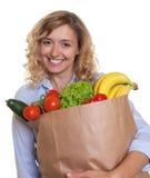 Frau mit dem gelockten blonden Haar und eine Tasche voll des gesunden Lebensmittels Lizenzfreie Stockfotos