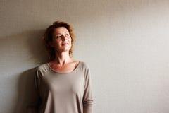 Frau mit dem gelockten Haar, das auf Wand in der Betrachtung sich lehnt lizenzfreie stockfotos
