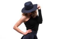 Frau mit dem gelockten Haar im schwarzen Hut und im stilvollen eleganten Abendkleid stockfotos