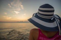Frau mit dem gestreiften Strohhut, der auf dem Ufer betrachtet sitzt stockbild