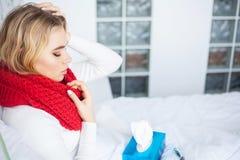 Frau mit dem Grippevirus, das im Bett liegt, misst sie ihre Temperatur mit einem Thermometer lizenzfreies stockbild