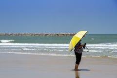 Frau mit dem großen Regenschirm, der auf jemand auf dem Strand wartet Stockbilder